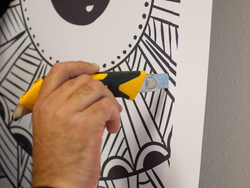 Als de hele sticker goed bevestigd is kun je de overtollige randen eraf snijden. Het makkelijkste is om het stanleymes strak tegen de deur te houden waarbij de punt iets naar buiten wijst. Zo kun je in een soepele beweging, het mesje rustend tegen de deur, naar beneden snijden.